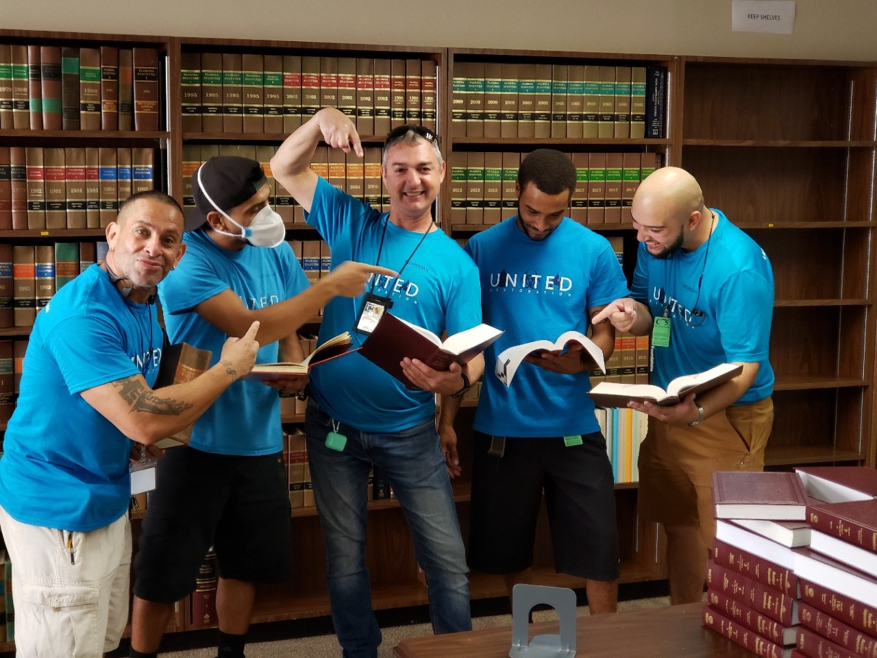 united restoration team members pose in broward county law library