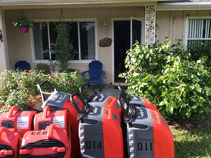 water damage restoration equipment in front of residential home