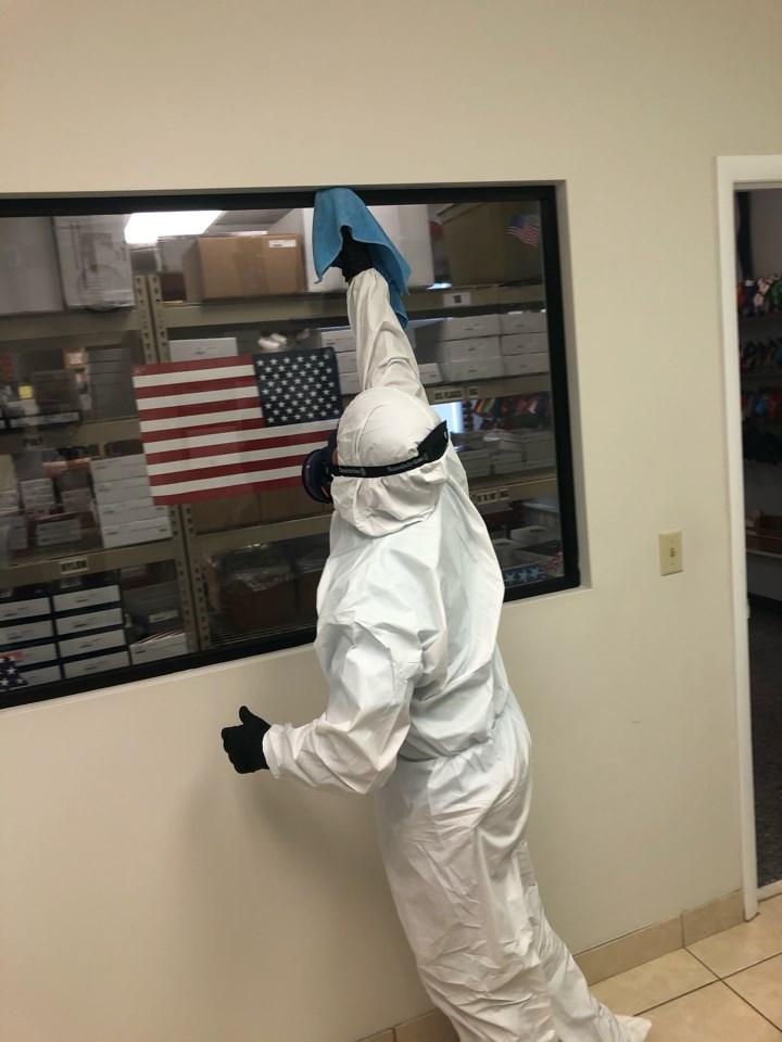 technician wiping down office for coronavirus