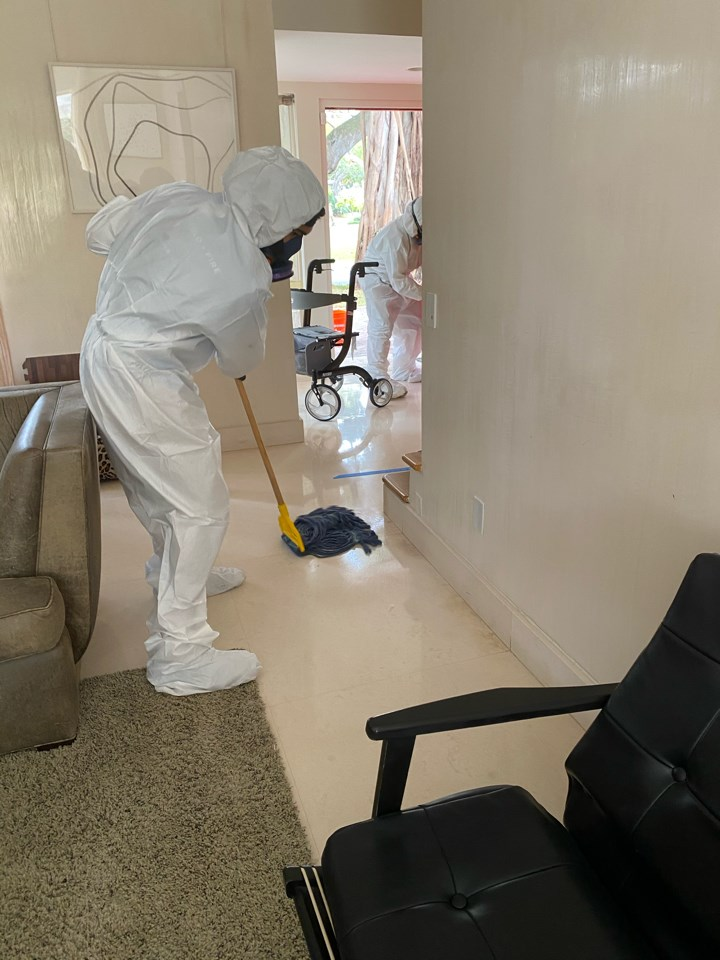 technician wiping down floor in miami home for covid-19