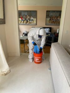 technician preparing covid-19 cleaning solution in bucket