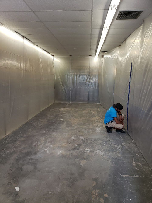water damage restoration technician installing containments